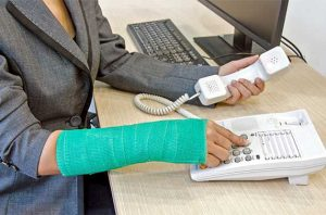 Photo of woman with a cast on her forearm and wrist dailing a telephone.