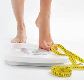 Photo of a women's feet as she steps on a weight scale. A tape measure is positioned on the upper side of the scale.