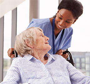 Photo of care provider assisting a women seated in a wheelchair.