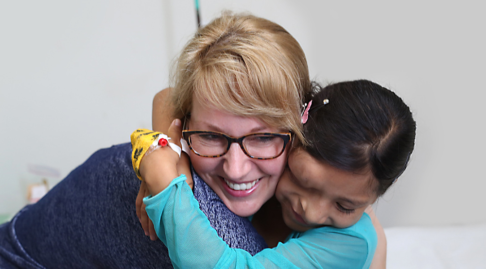 Dr. Jessyka Lightall is pictured receiving a hug from a young female patient in Peru in 2017. The young girl has lumps on her forehead and nose and an IV port in her hand, covered by tape. She is smiling with her eyes closed. Dr. Lightall is smiling. In the background, a hospital bed is seen.