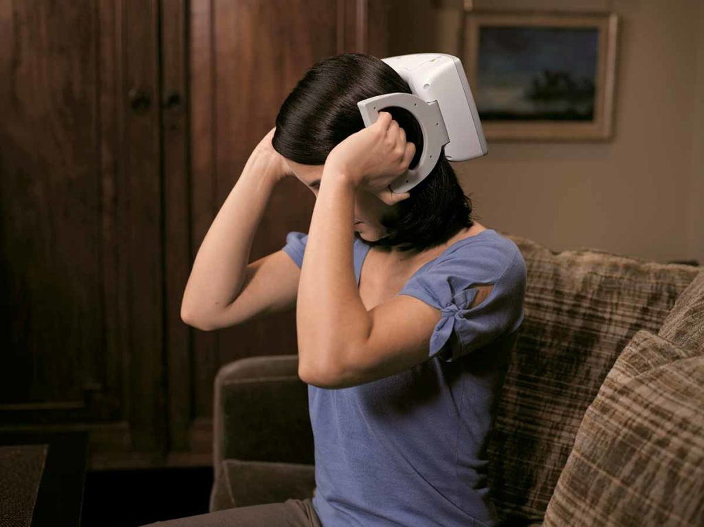 A young women holds a device up to the back of her head. It has handles that her hands are holding. The device is a single pulse transcranial magnetic stimulation for acute management of migraine pain.