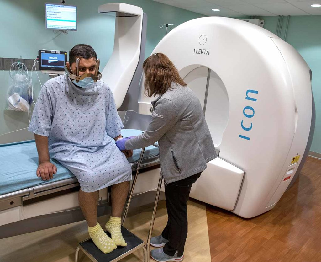 Man wearing blue hospital gown and yellow socks sits on an examination table. Woman with back to camera in a grey coat and black pants is preparing the patient for treatment with the Gamma Knife, which is shown in the background of the photo.