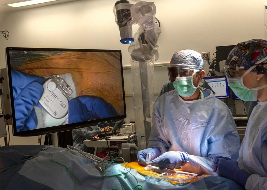 Two surgical team members wearing blue caps, green face masks and blue scrubs perform upper airway stimulation surgery on a patient using a 4K-3D exoscope that broadcasts an image of the implanted neurostimulator on a TV screen.