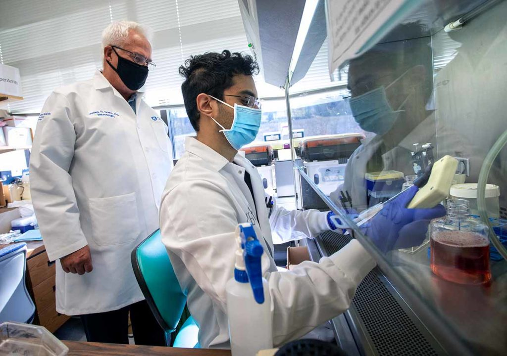 James Connor, distinguished professor of neurosurgery and anatomy and vice chair for research, Department of Neurosurgery, stands in his lab and looks over the shoulder of graduate assistant Ganesh Shenoy. Both are wearing face masks and white lab coats. Shenoy is holding a yellow device and wearing purple gloves.