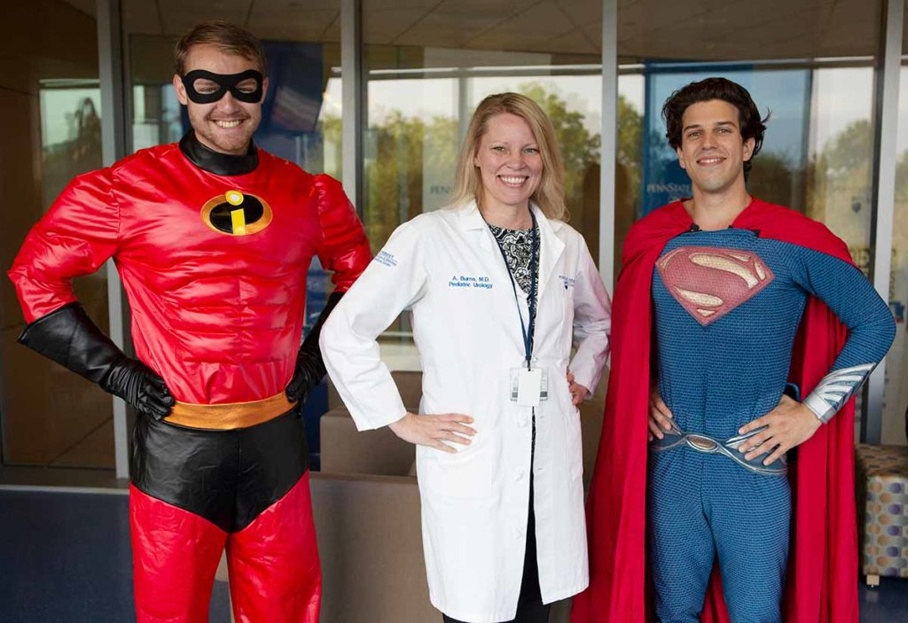 Medical students dressed as Mr. Incredible and Superman flank blonde physician wearing a white lab coat.