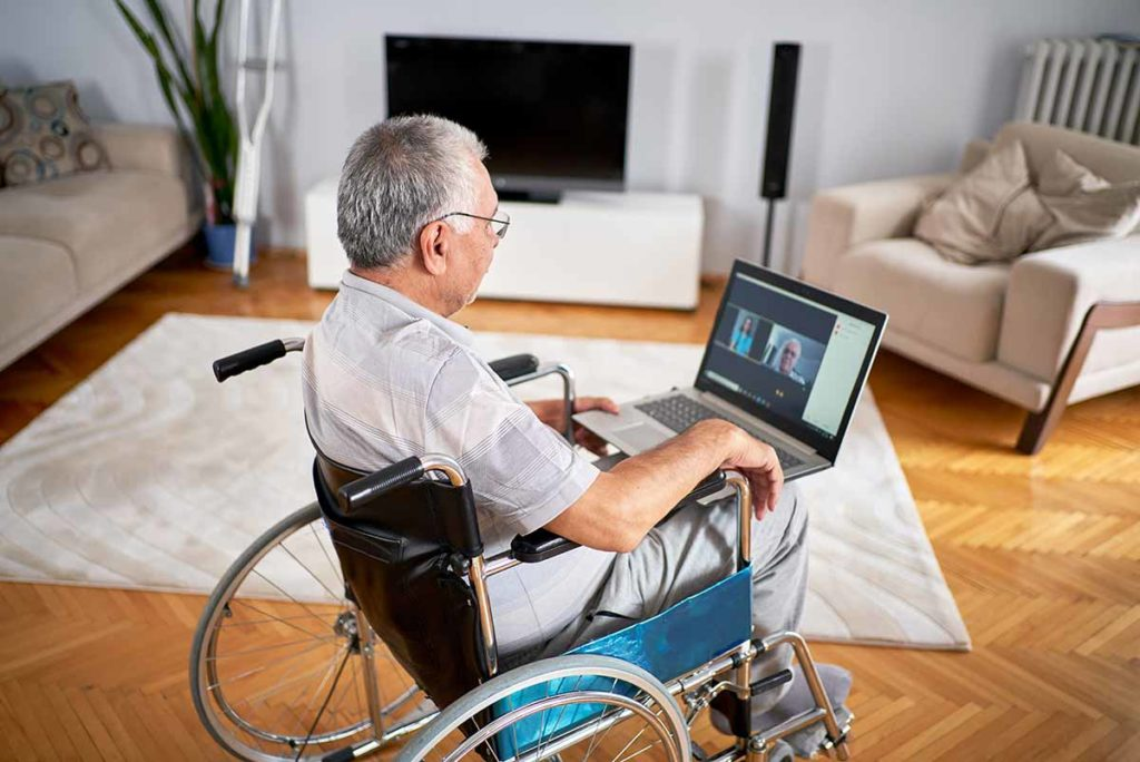 Older man sitting in wheelchair using laptop.